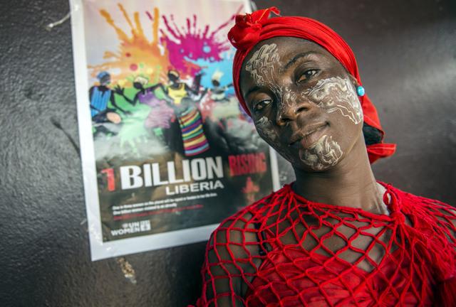 A Liberian traditional dancer takes a break